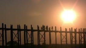 U Bein Bridge, Mandalay, Myanmar. U Bein Bridge at sunset with people crossing Ayeyarwady River, Mandalay, Myanmar stock video footage