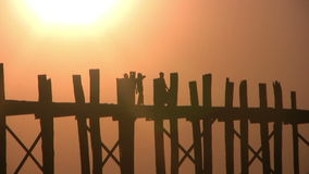 U Bein Bridge, Mandalay, Myanmar. U Bein Bridge at sunset with people crossing Ayeyarwady River, Mandalay, Myanmar stock video
