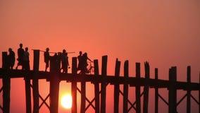 U Bein Bridge, Mandalay, Myanmar. U Bein Bridge at sunset with people crossing Ayeyarwady River, Mandalay, Myanmar stock footage