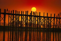 A munk is walking over the U Bein Bridge Mandalay. royalty free stock image