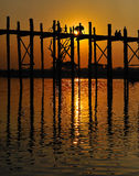 U bein bridge in myanmar. A silhoutte of figures walking across u bein bridge in mandalay,myanmar Stock Photos
