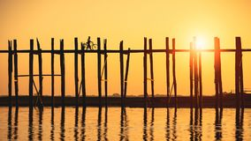 U bein bridge. Silhouette of people traveling across the U Bein Bridge in the evening. Mandalay Myanmar Stock Image
