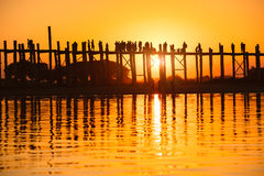 U bein bridge. Silhouette of people traveling across the U Bein Bridge in the evening. Mandalay Myanmar Royalty Free Stock Photography
