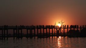 U Bein Bridge at sunset in Amarapura, Laos. Silhouettes crossing U Bein Bridge at sunset stock video footage
