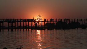 U Bein Bridge at sunset in Amarapura, Laos. Silhouettes crossing U Bein Bridge at sunset stock video