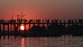 U Bein Bridge at sunset in Amarapura, Laos. Silhouettes crossing U Bein Bridge at sunset stock footage