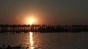 U Bein Bridge at sunset in Amarapura, Mandalay, Myanmar. Silhouettes crossing U Bein Bridge at sunset stock video footage