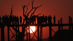 U Bein Bridge at sunset in Amarapura, Mandalay, Laos. Silhouettes crossing U Bein Bridge at sunset stock video