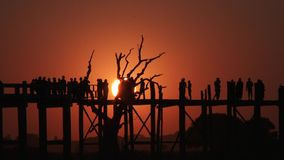 U Bein Bridge at sunset in Amarapura, Mandalay, Laos. Silhouettes crossing U Bein Bridge at sunset stock footage