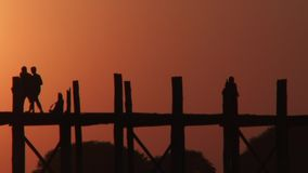 U Bein Bridge at sunset in Amarapura, Mandalay, Laos. Silhouettes crossing U Bein Bridge at sunset stock video footage
