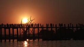 U Bein bridge at sunset in Amarapura, Mandalay, Myanmar. People crossing U Bein bridge at sunset stock video