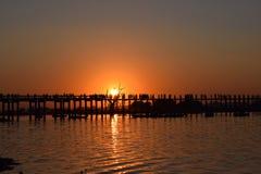 U Bein Bridge at sunset in Amarapura, Mandalay, Myanmar. Silhouettes crossing U Bein Bridge at sunset Royalty Free Stock Image