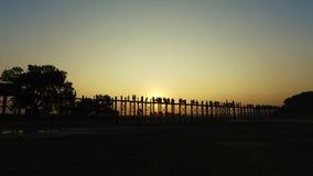 U Bein Bridge at Sunset, Myanmar. The villagers and tourists walking on U-Bein bridge at sunset stock video