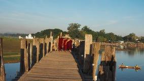 U-BEIN BRUG, AMARAPURA, MYANMAR 21 SEPTEMBER: Boeddhistische monniken op hun dagelijkse gang over de brug in de vroege ochtendure stock afbeelding