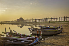 U-Bien Bridge and boats. Colorful traditional Asian boats on lakeshore with long wooden bridge in background under orange skies at sunrise royalty free stock photography