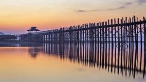 U-Bien Bridge dawn 1. Long wooden pedestrian bridge reflected in lake in orange light at sunrise stock photos