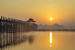 U-Bien Bridge sunrise. Sun rising to the right of wooden footbridge across lake with early morning mist on the water stock photo