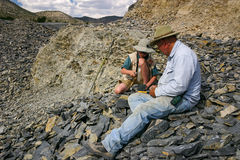 U-Dig Fossils. Quarry owner shows young boy how to excavate fossils at U-Dig Fossils in Delta, Utah stock photo
