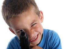 U jongen in heldere blauwe kleding met stuk speelgoed kanon Stock Fotografie