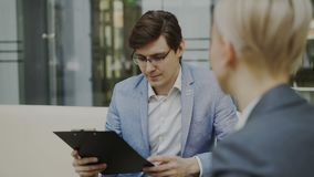 U-manager die met klembord jonge vrouwelijke kandidaat voor het huren op lege positiezitting interviewen op bank in modern stock video