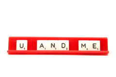 U and me. Scrabble pieces spelling the word U AND ME on a red board Royalty Free Stock Photos