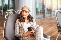 U?miechni?ta kobieta w lotniskowej kawiarni z fili?anka kawy fotografia stock