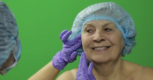 U?miechni?ta starsza kobieta w ochronnym kapeluszu Chirurg plastyczny sprawdza kobiety twarz zbiory