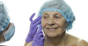 U?miechni?ta starsza kobieta w ochronnym kapeluszu Chirurg plastyczny sprawdza kobiety twarz zdjęcie wideo