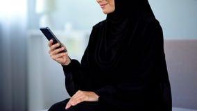 U?miechni?tej arabskiej kobiety smartphone czytelnicza wiadomo??, online komunikacja, gaw?dzenie obraz stock