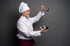 U?miechni?ty dojrza?y m?ski szef kuchni z pucharem i kulinarnym vane w r?kach na czarnym tle zdjęcia royalty free