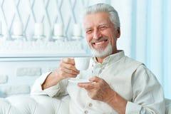 U?miechni?ty starszy m??czyzna pije kaw? w domu zdjęcia stock