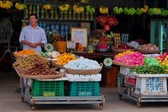 U?miechni?ty uliczny owocowy sprzedawca, kosze z tropikalnymi owoc, uliczny handel w Azja Po?udniowo-Wschodnia zdjęcia stock