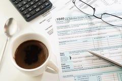 U S 收入税单形式、咖啡,笔、计算器和玻璃 库存照片