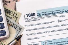 U S 1040纳税申报与笔、美元和计算器的2017年 免版税库存图片