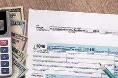 U S belastingaangifte 1040 voor het jaar van 2017 met pen, dollar en calculator Stock Afbeelding
