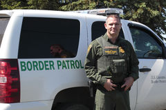 A U.S. Border Patrol Officer. A United States border patrol officer working for Homeland Security stands beside his vehicle Royalty Free Stock Image
