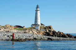 U.S. Coast Guard Lighthouse in Boston Harbour. A costumed guide stands on the rocky shore of the United States Coast Guard Lighthouse Station islet off the coast Royalty Free Stock Photos