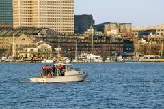 U.S. Coastguard ship patrols Boston Harbor and the Boston skyline from terrorists at sunrise as seen from South Boston, Massachuse Stock Photo