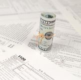 1120 U.S. Corporation income tax return form with roll of american dollar banknotes. Close up. Concept of tax period in United States royalty free stock photo