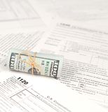 1120 U.S. Corporation income tax return form with roll of american dollar banknotes. Close up. Concept of tax period in United States royalty free stock photos