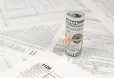 1120 U.S. Corporation income tax return form with roll of american dollar banknotes. Close up. Concept of tax period in United States stock image