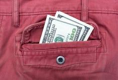U S Dólares no bolso traseiro das calças de brim Fotografia de Stock Royalty Free