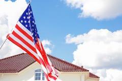 U.S.A. d'ondeggiamento inbandiera ed alloggia il tetto con cielo blu Fotografia Stock