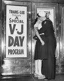 U S de zeeman en zijn meisje vieren nieuws van het eind van oorlog met Japan voor het Theater trans-Lux in Sq de Tijd van New Yor royalty-vrije stock foto