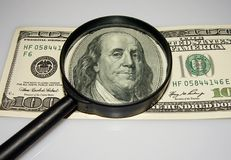 U.S. dollars and a Magnifying glass. Royalty Free Stock Photo