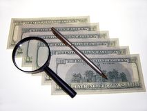 U.S. dollars and a Magnifying glass. Stock Images