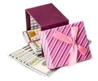 U S dollarsbankbiljetten die in rode boog verfraaide giftdoos leggen Stock Fotografie