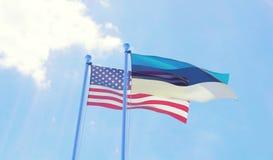 U.S.A. e bandiere dell'Estonia che ondeggiano contro il cielo blu Fotografia Stock