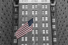 U.S. Flag and brick building. Flag flying in front of brick urban hotel Royalty Free Stock Images