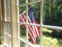 U.S. Flag through window. A United States flag through a window.  Nice view of a front yard with a beautiful red, white and blue flag prominently displayed Stock Image